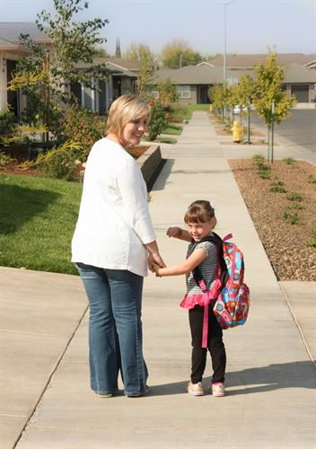 Photo of mom and daughter walking to school.